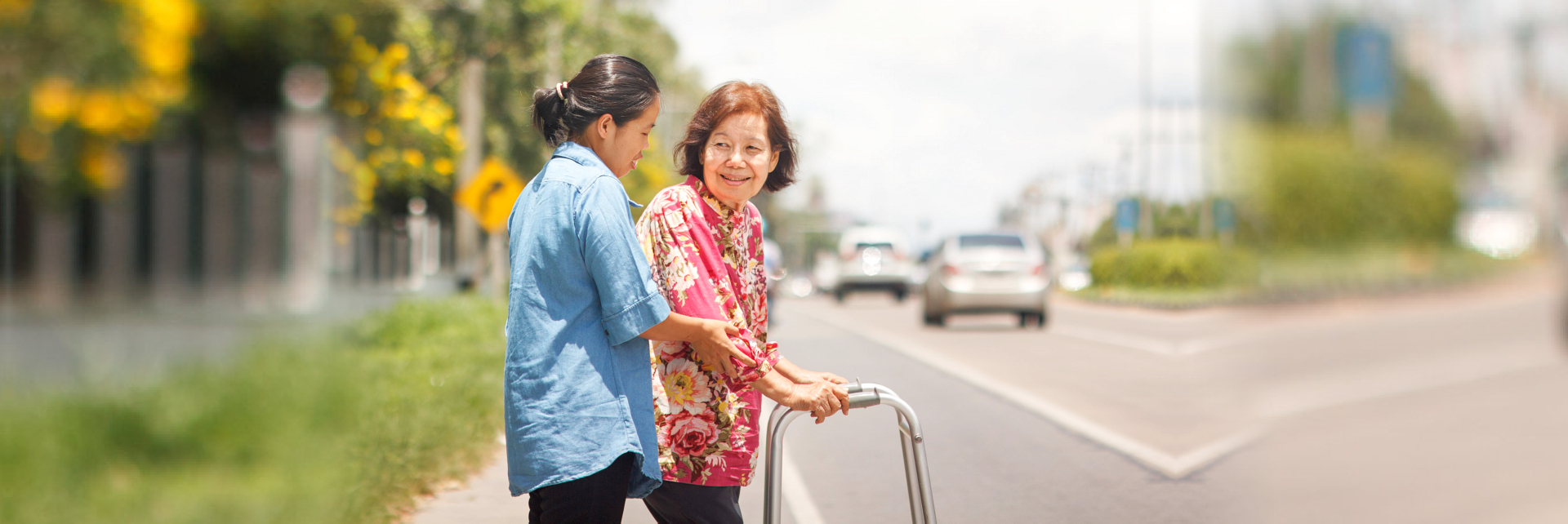 lady assisting elderly woman in crosing the street