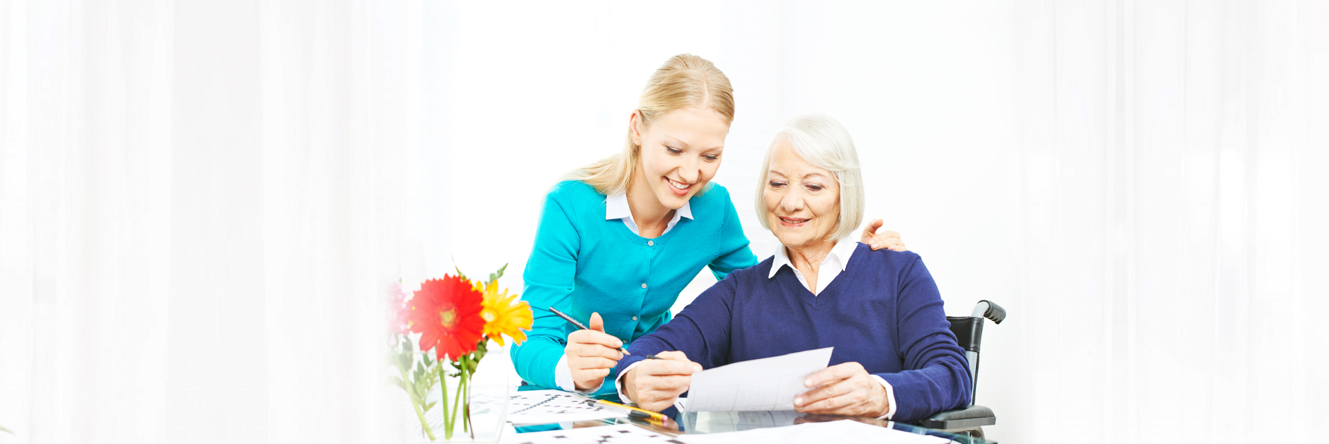 caregiver assisting senior woman in writing
